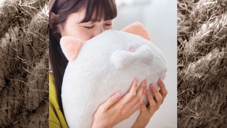 A woman presses her face against a cat head-shaped pillow.