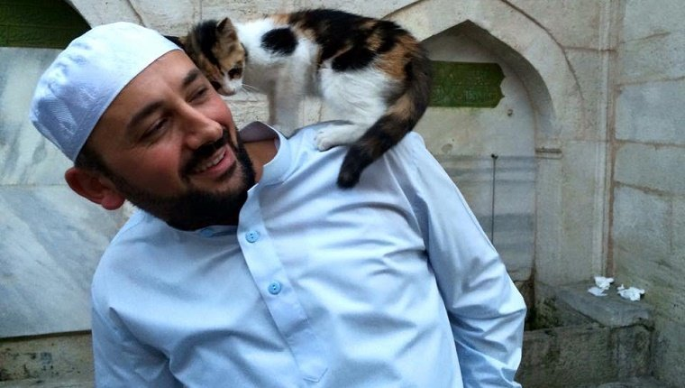 A small cat stands on Imam Mustafa Efe's shoulder outside of the mosque.
