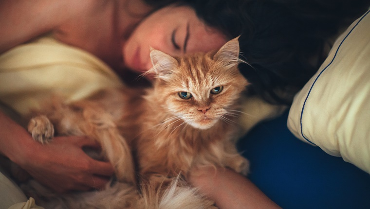 Woman embracing her cat while sleeping.