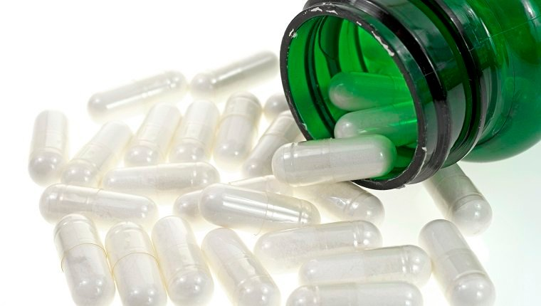 A close view of several acidophilus capsules spilling from a green vitamin bottle.