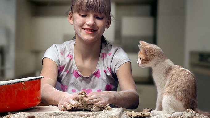 kitten watching girl kneading dough